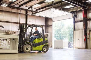 An O'Mara team member operates a forklift to move equipment around in the warehouse.