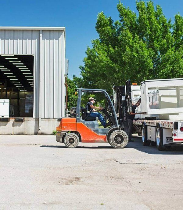 A team member operates a forklift to load a truck with newly manufactured ag system parts.