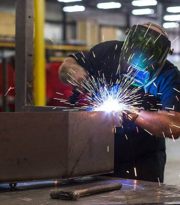 An O'Mara employee wears a mask as he welds metal pieces together.