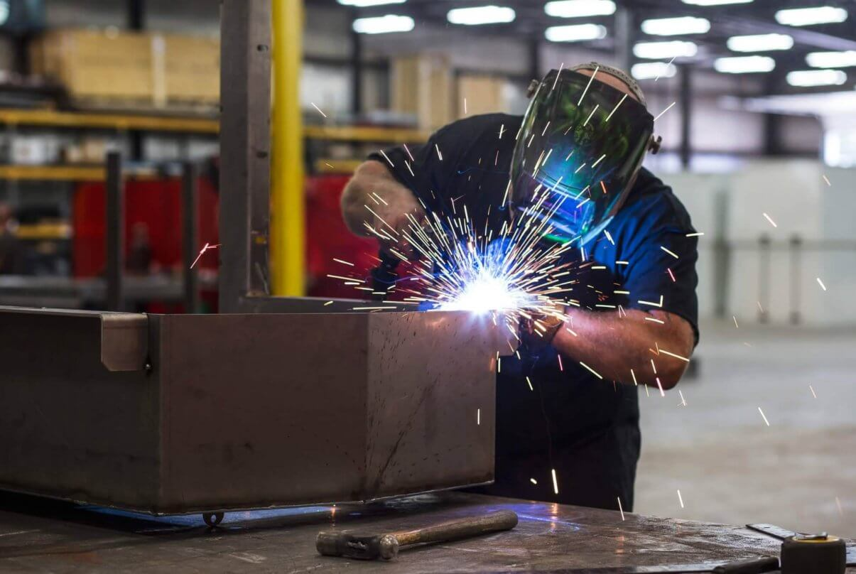 An employee wears a welding masks and sparks fly as he fuses sheets together.